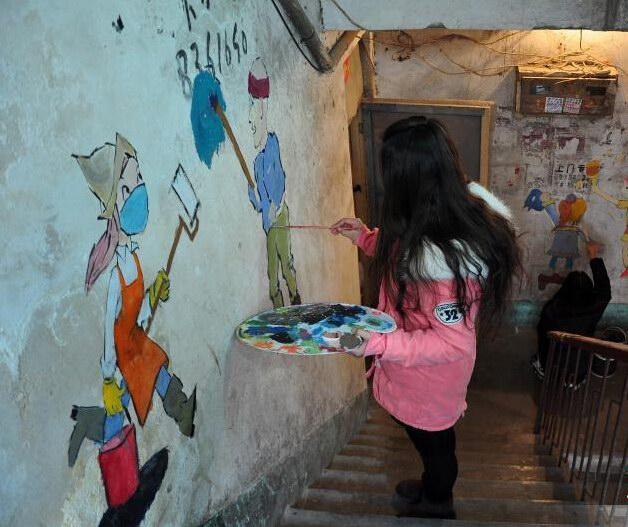 """山东聊城90后大学生楼道墙绘 小广告变身""""画壁"""""""